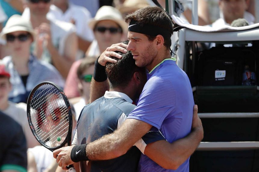 Spain's Nicolas Almagro (left) is comforted by Argentina's Juan Martin Del Potro as he has to give up.