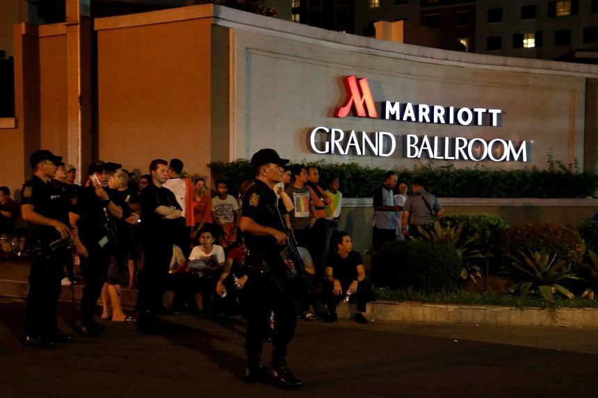 Policemen stand guard near evacuated employees of a hotel.
