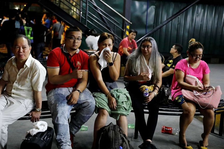 Tourists are pictured after being evacuated from a Resorts World building in Pasay City, Metro Manila.