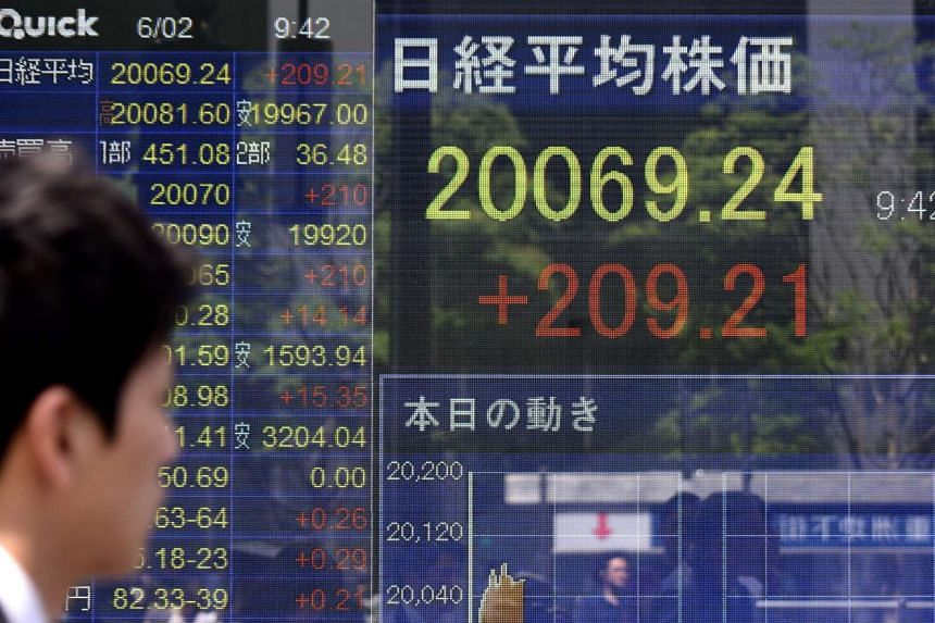 A man looks at a stock quotation board flashing the key Nikkei index of the Tokyo Stock Exchange.