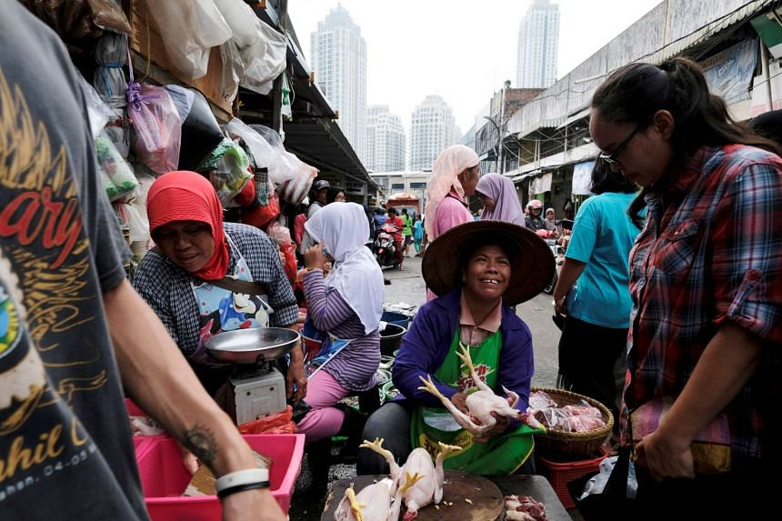 A seller offers a chicken to a customer at a vegetable market in Jakarta, Indonesia, on June 2, 2017.