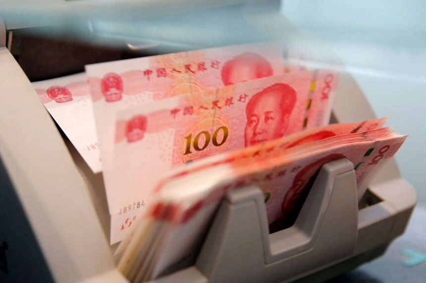 Chinese 100 yuan banknotes are seen in a counting machine while a clerk counts them at a branch of a commercial bank in Beijing, China.
