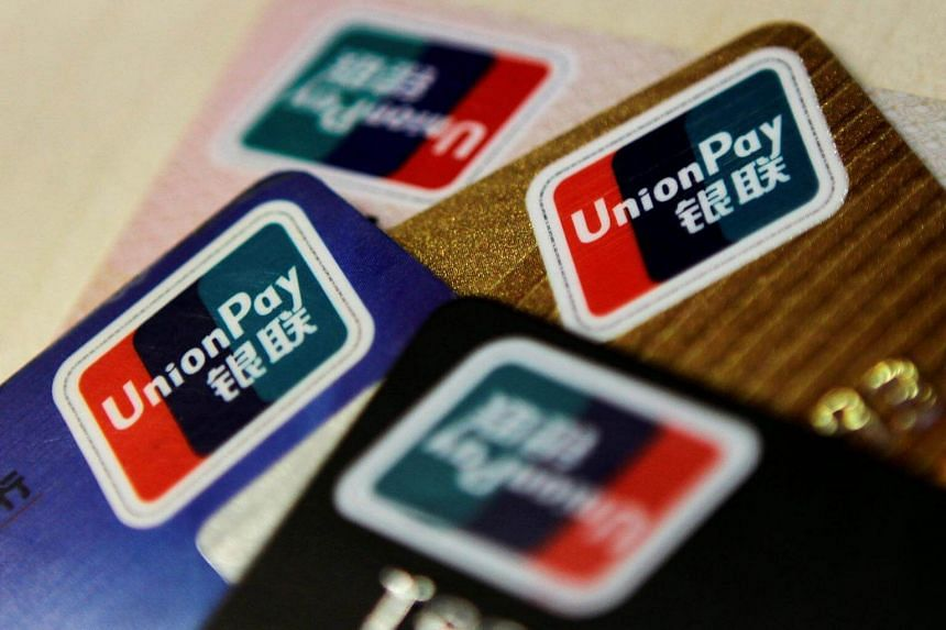 Logos of China UnionPay are seen on bank cards in this photo illustration taken in Beijing.