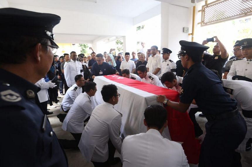Police officers cover the body of Staff Sergeant Nadzrie Matin with the national flag at void deck of an HDB block in Choa Chu Kang Ave 5.