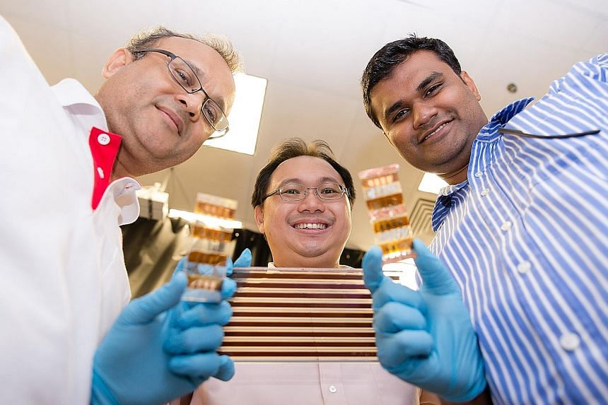 (From left) NTU's Energy Research Institute executive director Subodh Mhaisalkar with Associate Professor Sum Tze Chien and Assistant Professor Nripan Mathews. The trio are part of a team of scientists studying perovskites, which could be used in mak