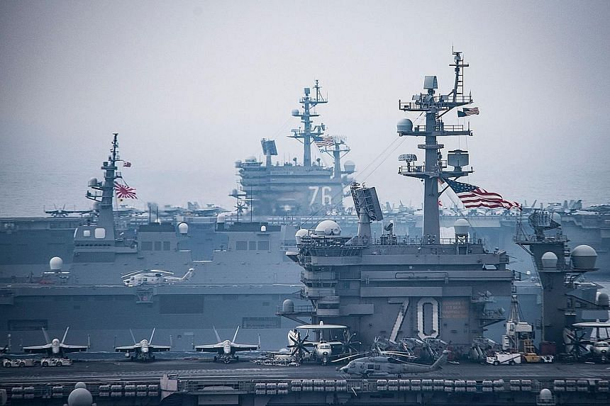 The United States' aircraft carriers USS Carl Vinson (No. 70) and USS Ronald Reagan (No. 76) sailing in side by side in waters off the Korean peninsula in the Sea of Japan yesterday. The carriers and their strike groups were conducting a joint exerci