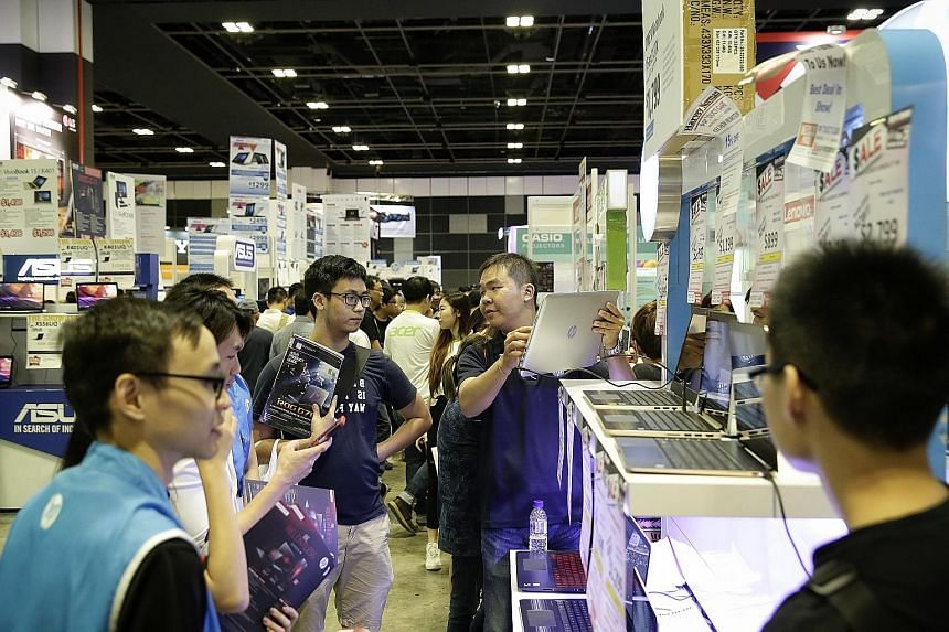 Right: Visitors browsing for deals at a booth selling laptops during the Consumer Electronics Exhibition 2017 at Suntec Singapore yesterday. Above: Seven-year-old Reem Firoz yesterday trying out the Samsung Gear VR 2017 edition at the annual PC Show,