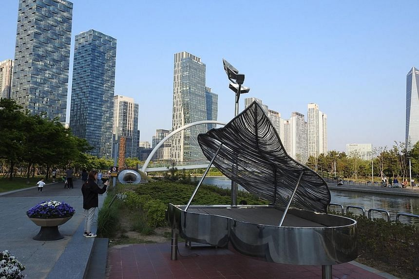 """A """"magic piano"""" that is a favourite among visitors to Central Park. It plays music on its own, but also responds to touch via a plastic keyboard. Left: Poles in the park are equipped with closed-circuit television cameras and siren bells to offer eme"""