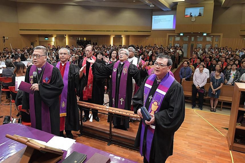 "Bishop Chong Chin Chung (with arms outstretched) at his consecration service in Commonwealth Drive last December. Bishop Chong said a home-grown minister offers ""context-based preaching that is sensitive to local situations and cultures"". Other Chris"