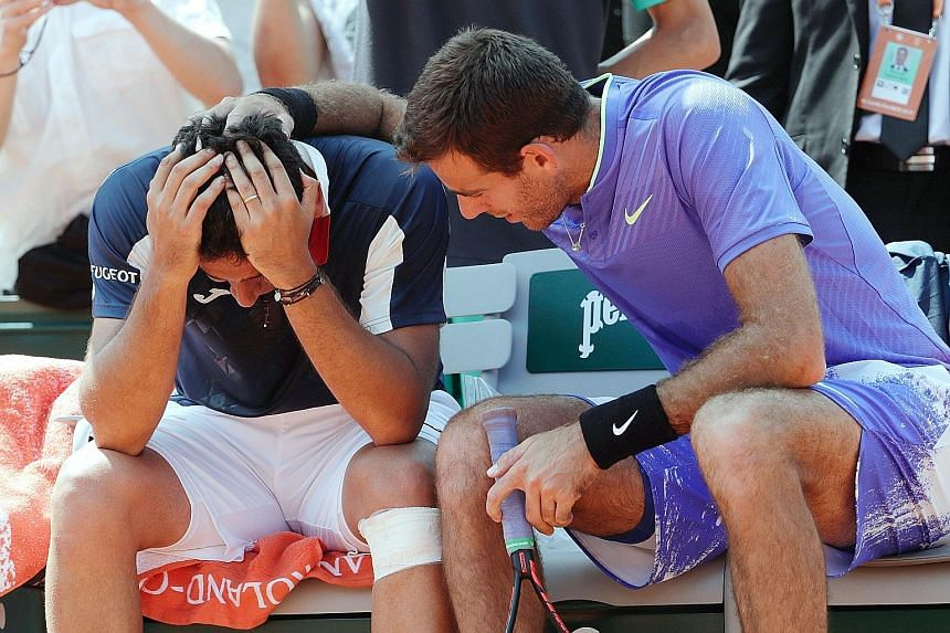 Nicolas Almagro being comforted by Juan Martin del Potro of Argentina after the Spaniard had to quit their French Open second-round match yesterday due to a left-knee injury.