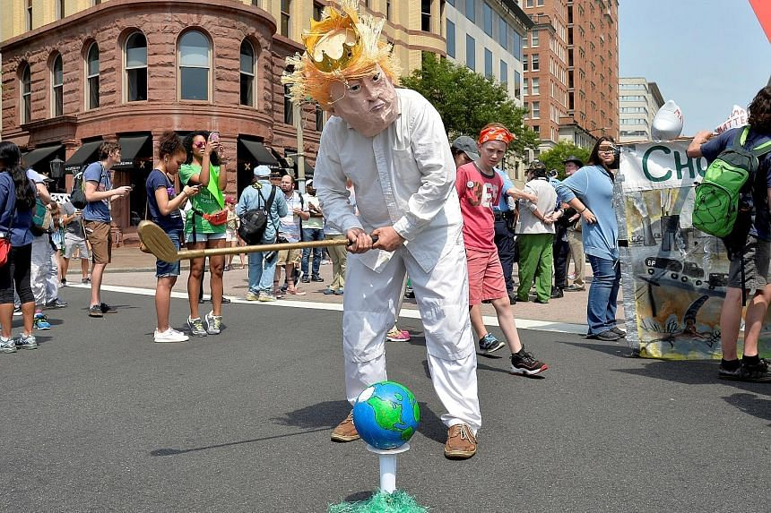 """A protester in a costume depicting US President Donald Trump and """"earth"""" on a golf tee joining demonstrators walking down Pennsylvania Avenue in Washington on April 29 during a People's Climate March to protest against Mr Trump's stance on the enviro"""