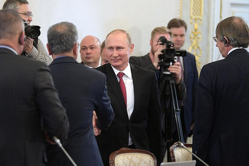 President Vladimir Putin meeting with heads of international news agencies on the sidelines of the St Petersburg International Economic Forum at the Konstantinovsky Palace yesterday.