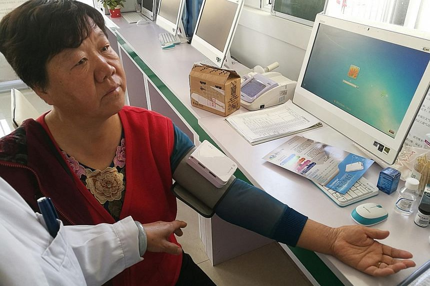 Retiree You Yulan gets her blood pressure tested at a community medical exam clinic within her condo Future City, one of 20 smart communities in Yinchuan, central China.