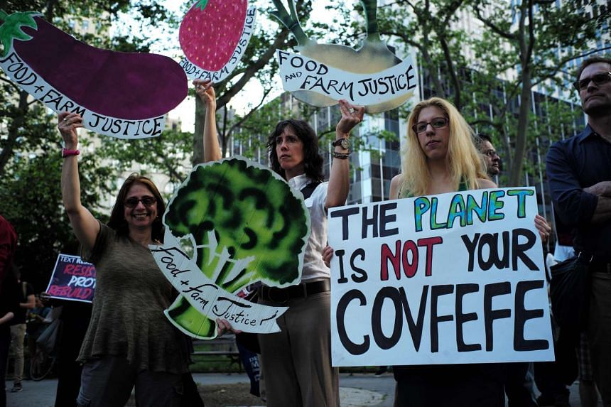 Environmental activists and supporters display placards during a demonstration in New York to protest Donald Trump's decision to pull out of the Paris climate accord deal.