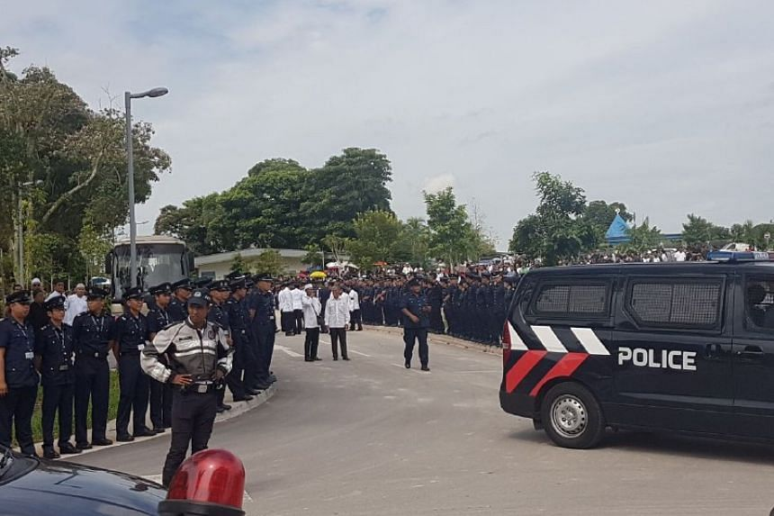 TP officers watches on as the body of their colleague Nadzrie Matin is brought onto a bus for its journey to a nearby mosque and Muslim cemetery.