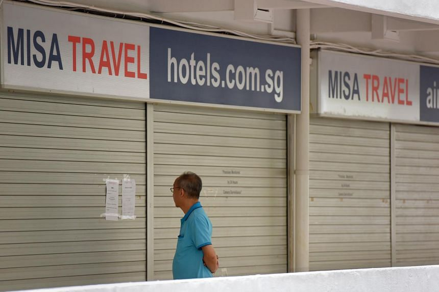 A passerby walks past the Misa Travel office, which put up a notice on their shutters indicating they were no longer in business.