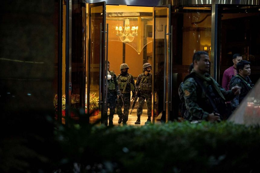 Philippines' police officers coming out from the Resorts World Hotel in Manila, on June 2, 2017.