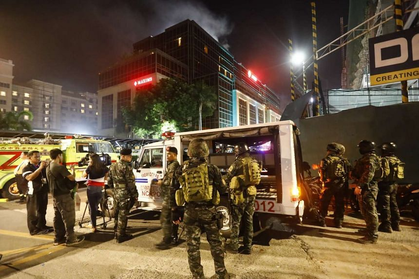 Smoke rising from the The Resorts World Manila hotel and casino complex as police maintain security in Pasay City, on June 2, 2017.
