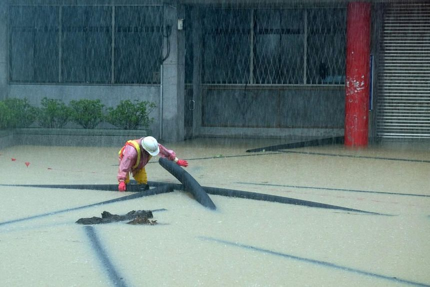 A worker sorting out pipes in a flooded street during heavy rain in Jinshan, New Taipei City on June 2, 2017.