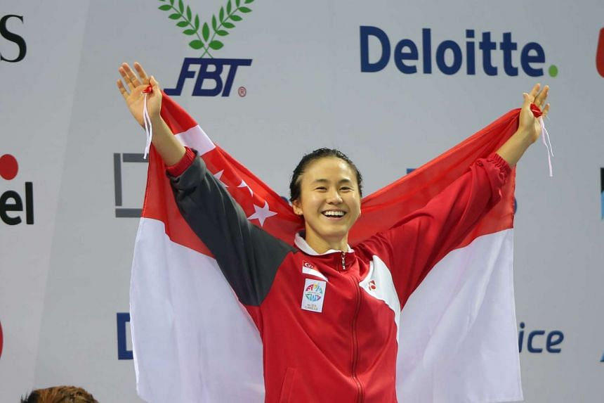 Singapore swimmer Quah Ting Wen raises her hands in celebration after winning the gold medal in the women's 100m freestyle at the 28th Sea Games on June 8, 2015.