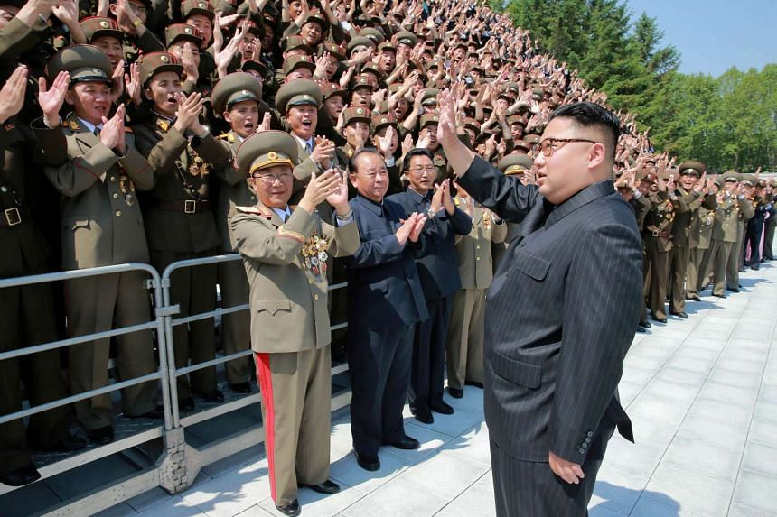North Korean leader Kim Jong Un waves to missile scientists and technicians.