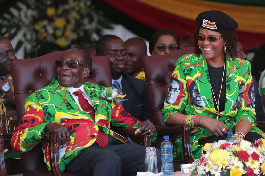 Mugabe (left) and wife Grace (right) smile after arriving at the rally venue. June 2, 2017.