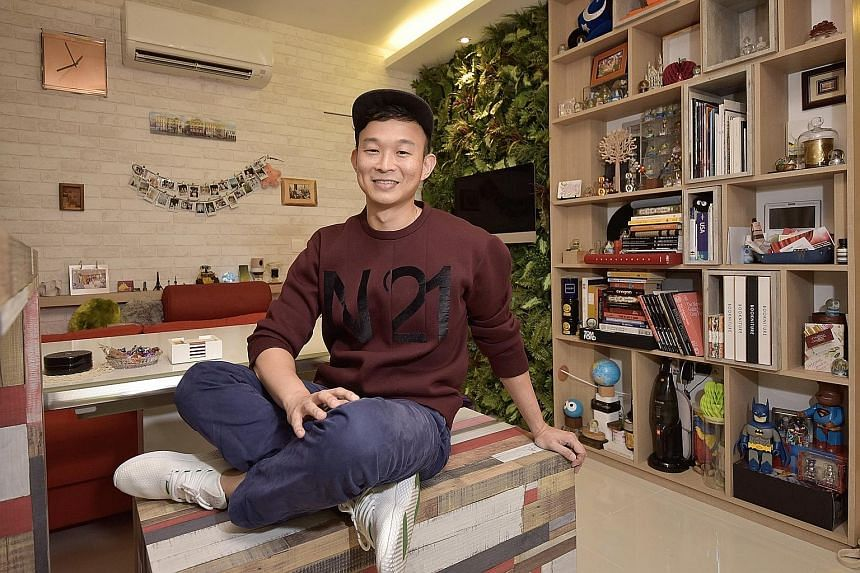 The loud colours of the kitchen cabinets complement the lime-green Smeg fridge. Fake lawn grass and potted plants decorate the balcony where the washing machine and dryer are. Mr Wee Ng on a custom-made bench that doubles as a storage compartment.