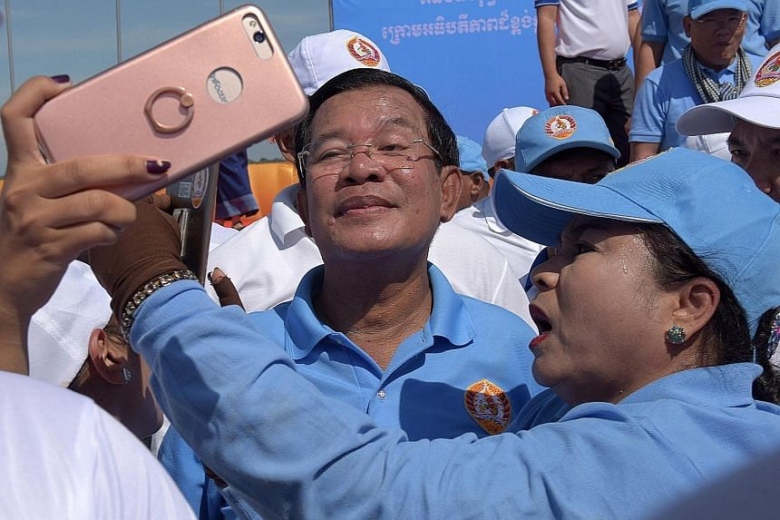 Cambodian Prime Minister Hun Sen posing for photos with supporters of the Cambodian People's Party on the last day of the commune election campaign in Phnom Penh yesterday. The local polls are set to test the mettle of an opposition desperate to upen