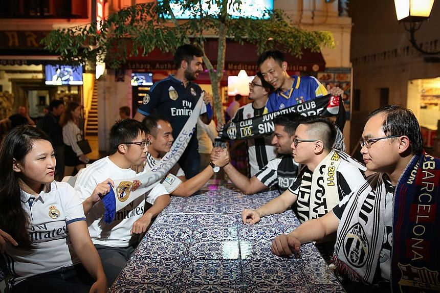 Real Madrid (left) and Juventus fans squaring off at the Sahara Bar & Restaurant, the venue where local Juve supporters will congregate to watch the Champions League final tonight.