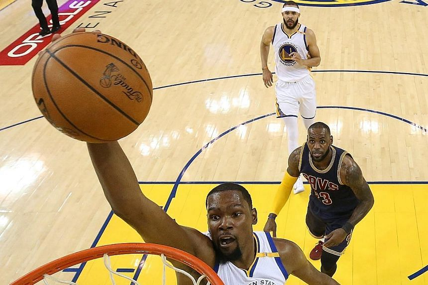 Golden State Warriors forward Kevin Durant goes in for a dunk against the Cleveland Cavaliers in the first half of the NBA Finals opener. He had six in the first half, setting a one-game career record.