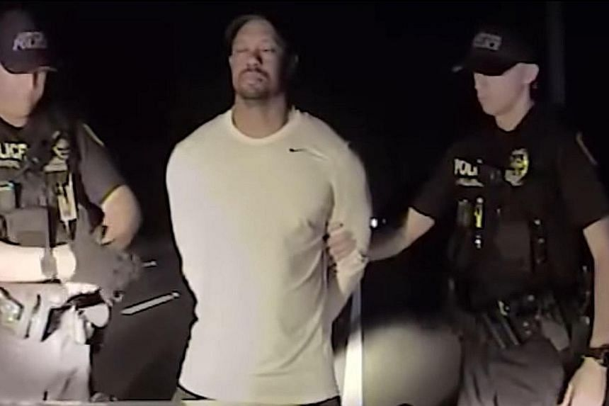 This still image from a police vehicle dash-cam video released by the Jupiter, Florida, police department shows officers arresting former world No. 1 Tiger Woods on Monday. He wobbled as he tried to walk along a straight line in a field sobriety test