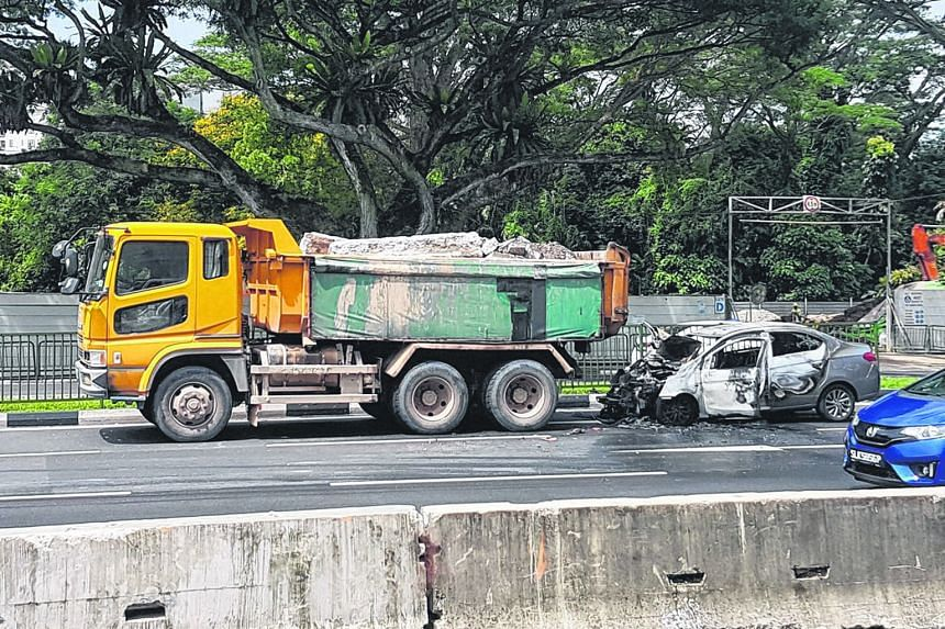 A grey Mitsubishi car in flames near the junction of Clementi Road and Clementi Avenue 2 yesterday afternoon. It is understood that it collided with a tipper truck before bursting into flames.