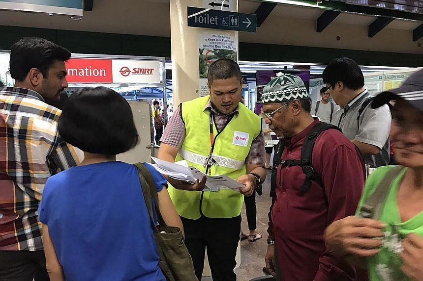 An SMRT employee in Yishun handing out pamphlets on alternative modes of transport to commuters yesterday. The delays yesterday and on Thursday were caused by two unrelated faults uncovered during checks on the line's new signalling system.