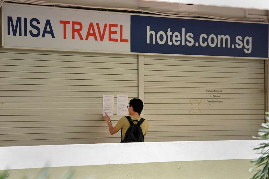 A passerby walking past Misa Travel's office at Hong Lim Complex, which has a notice on their shutters indicating that they were no longer in business.