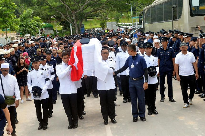 About 50 police officers sent off Staff Sergeant Nadzrie at his Choa Chu Kang home on Friday, with 11 pallbearers bearing his coffin, which was draped with the national flag.