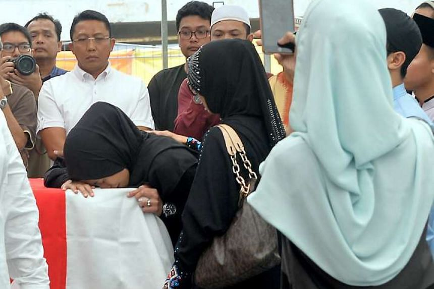 A grieving relative at Choa Chu Kang Muslim Cemetery, where Staff Sgt Nadzrie was laid to rest. Hundreds gathered at the officer's home, Al-Khair Mosque and the cemetery to bid a final farewell.