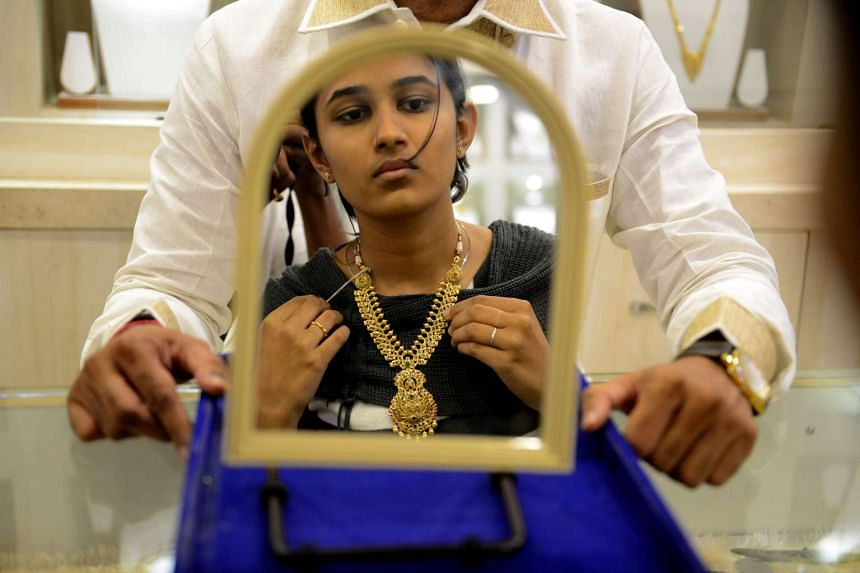 An Indian customer tries on gold items at a jewellery shop in Hyderabad, April 28, 2017.
