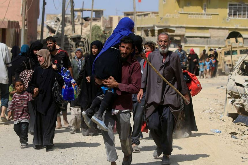 A displaced Iraqi fleeing clashes, carries a woman in western Mosul, June 3, 2017.