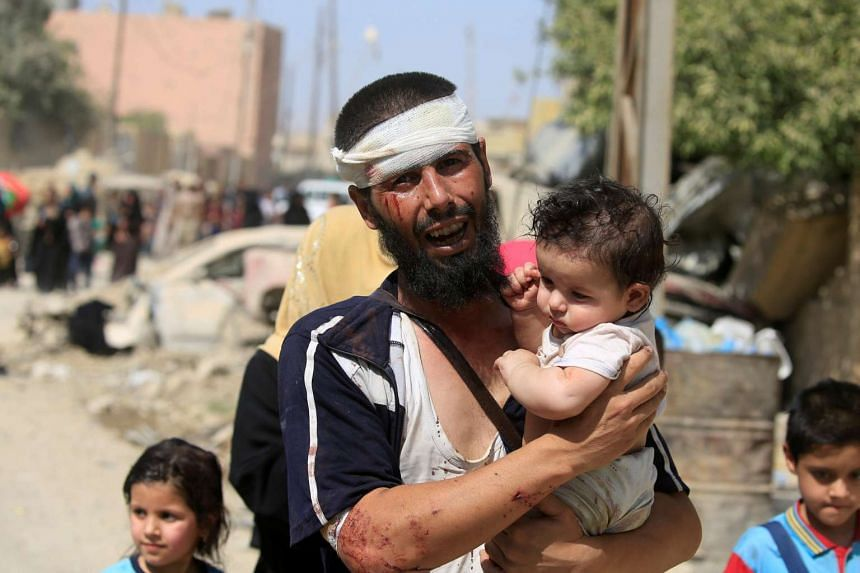 A displaced Iraqi fleeing clashes, carries his child in western Mosul, June 3, 2017.