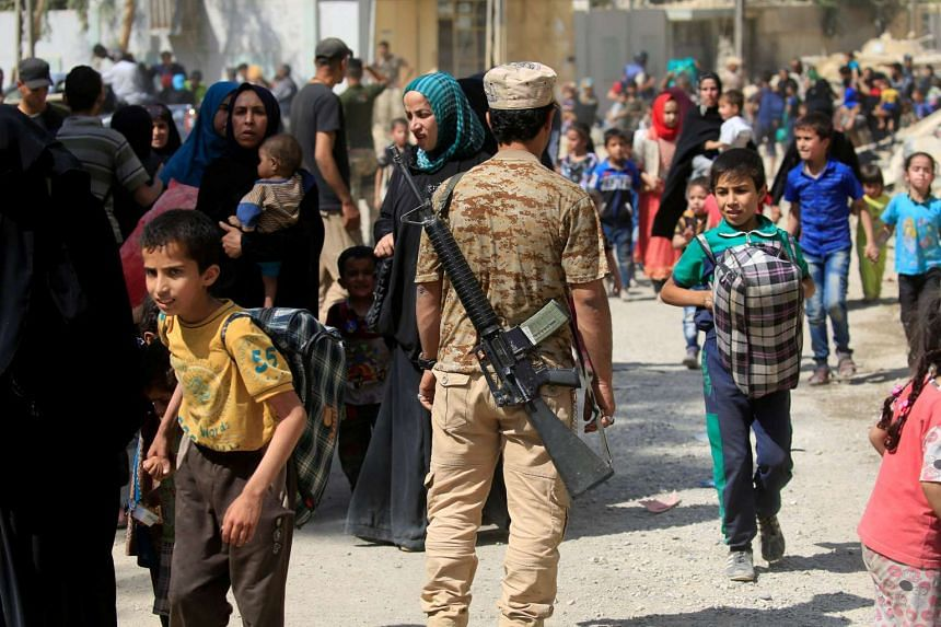 A member of the Iraqi rapid response forces stands guard as displaced people walk by. in western Mosul, June 3, 2017.
