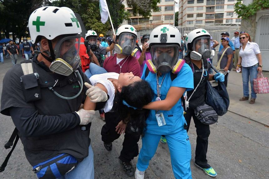 A woman is carried away by medical staff in Caracas on June 3, 2017.