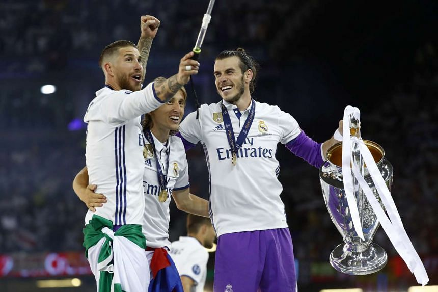 Sergio Ramos, Gareth Bale and Luka Modric celebrate with the trophy.