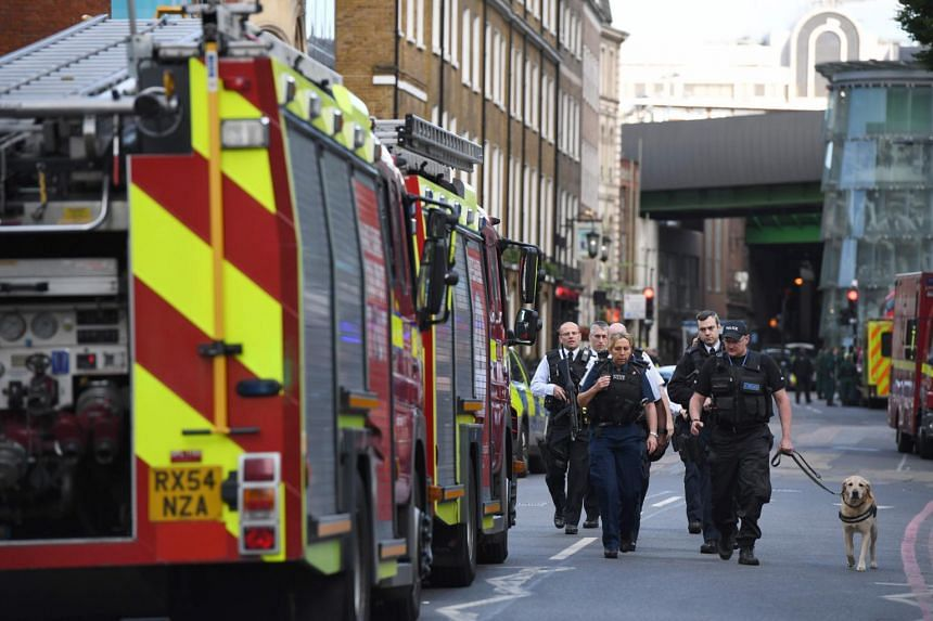 Armed police officers patrolling the streets from Borough Market towards The Shard in London on June 4.