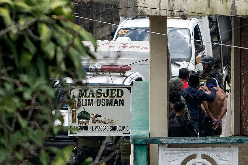 Above: ISIS-influenced suspects being arrested in a Marawi City village yesterday. Below: A soldier carrying a child who was trapped with her family for 11 days at Marawi's Pangarungan Village.