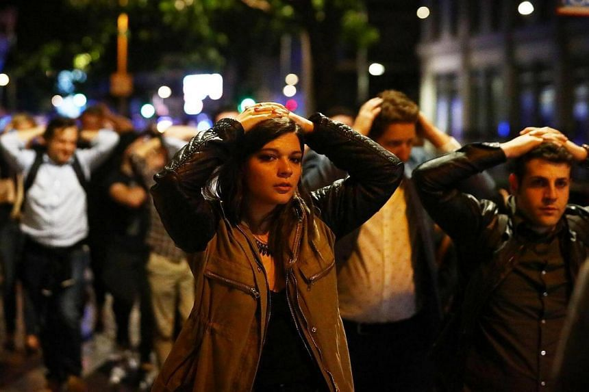 People leave the area with their hands up after an incident near London Bridge in London, Britain on June 4, 2017.