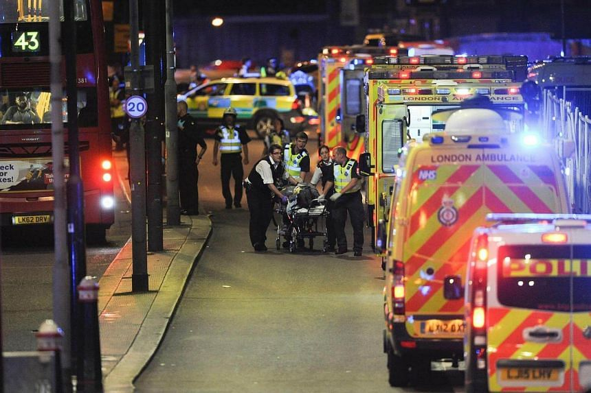 Police officers and members of the emergency services attend to a person injured on London Bridge on June 3, 2017.