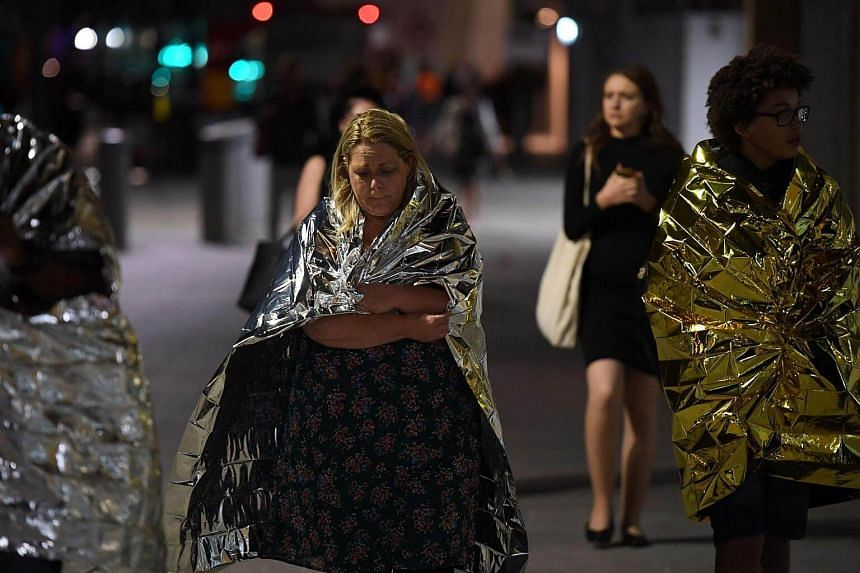 Members of the public, wrapped in emergency blankets leave the scene of a terror attack on London Bridge in central London, on June 3, 2017.