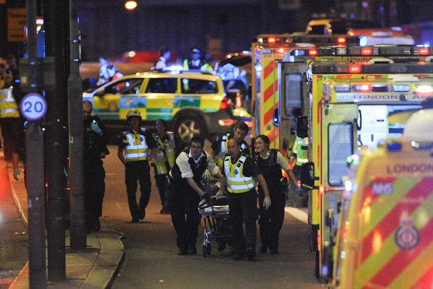 Police officers and emergency services personnel attending to a person injured during the attack on London Bridge, on June 3, 2017.