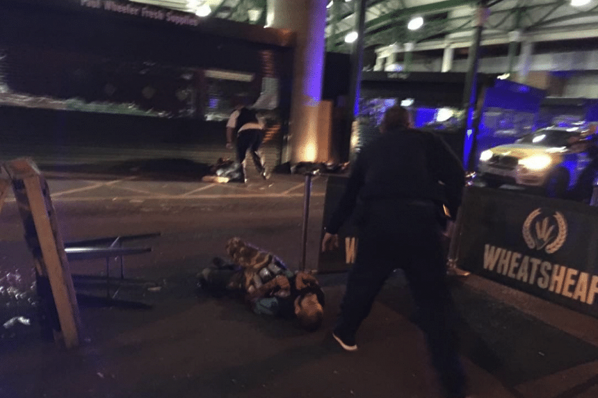 One of the men suspected of being behind the deadly attack was shown in a photograph lying on the ground with canisters strapped to his body after he was shot by the police.