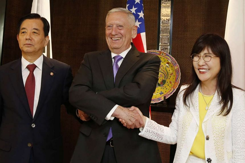 South Korean Minister of Defense Han Min Goo (left), US Secretary of Defense James Mattis (centre) and Japanese Defense Minister Tomomi Inada shake hands during the International Institute for Strategic Studies (IISS) 16th Asia Security Summit in Sin